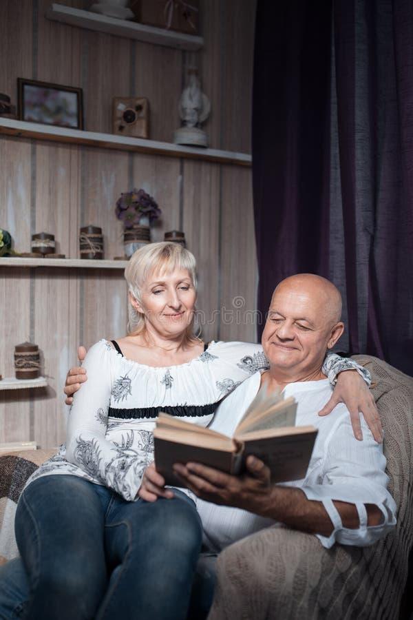 De gelukkige oudsten koppelen zitting als voorzitter en lezen boek; royalty-vrije stock foto's