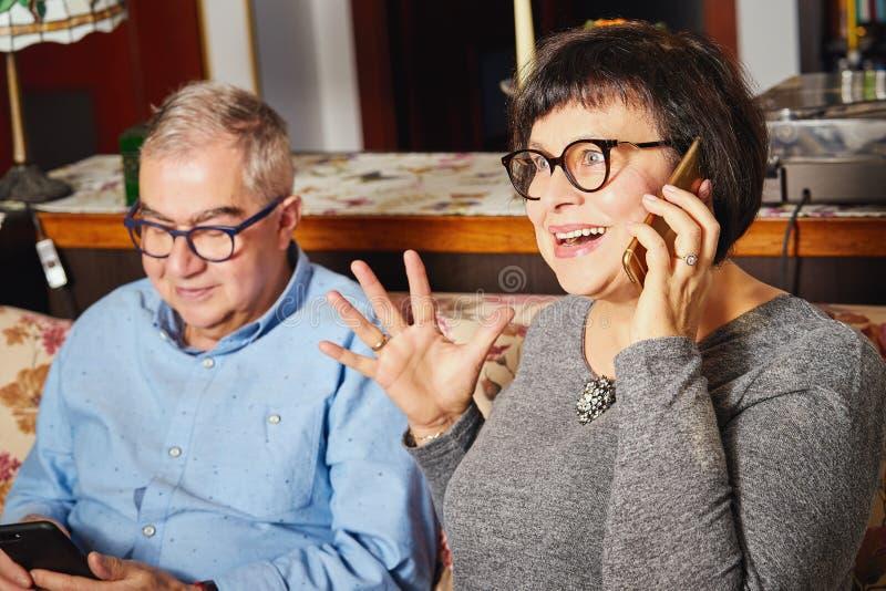 De gelukkige oudsten koppelen zitting op de laag terwijl vrouw het spreken op de telefoon royalty-vrije stock afbeeldingen