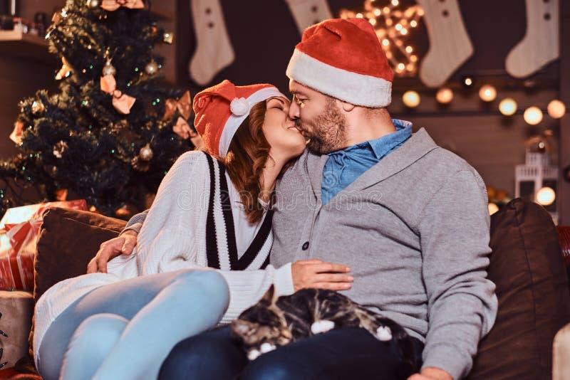 De gelukkige paar het vieren Kerstavond kust thuis terwijl het zitten op bank de Kerstman en rode bal royalty-vrije stock afbeeldingen