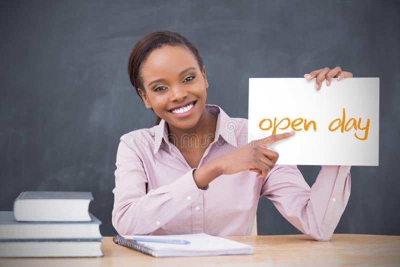 De gelukkige pagina die van de leraarsholding open dag tonen stock fotografie