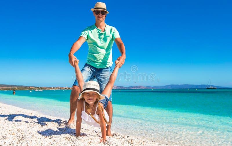 De gelukkige papa en het meisje hebben pret op tropisch stock fotografie