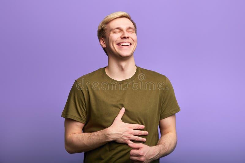 De gelukkige positieve mens raakt maag, kan t ophouden lachend royalty-vrije stock afbeeldingen