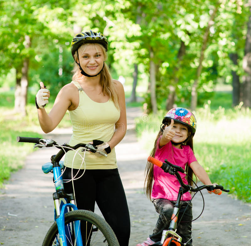 De gelukkige pret hebben, een fiets berijden en moeder en dochter die beduimelen omhoog de tonen royalty-vrije stock afbeelding