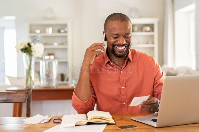 De gelukkige rekening van de mensenlezing en het spreken op telefoon royalty-vrije stock fotografie