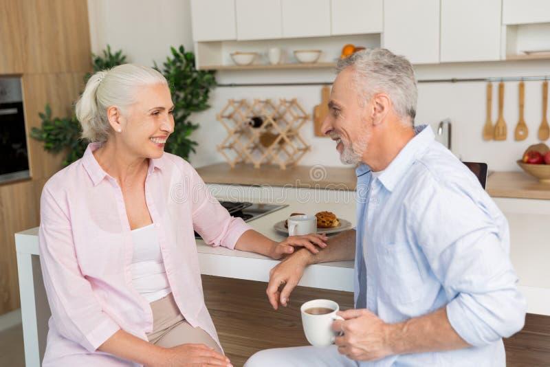 De gelukkige rijpe het houden van zitting van de paarfamilie bij de keuken stock foto's