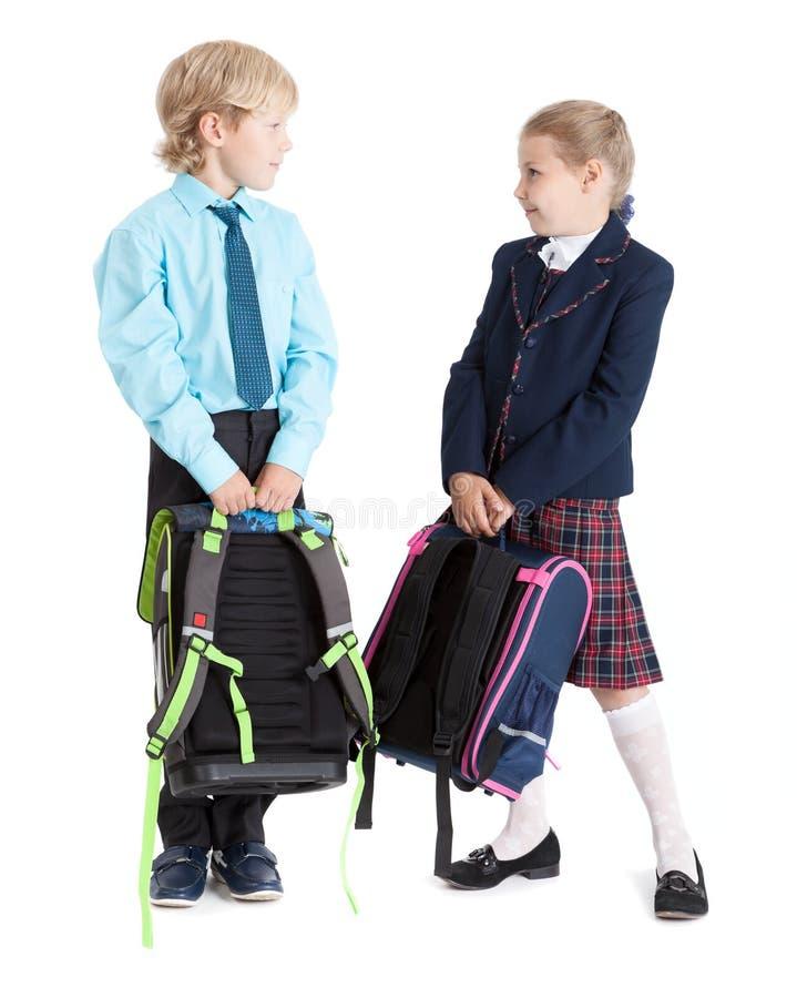 De gelukkige schoolkinderen in school eenvormig met schooltassen die elkaar, volledige lengte, isoleerden witte achtergrond kijke stock afbeelding