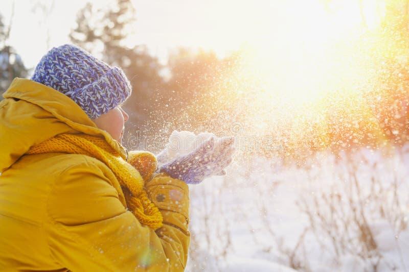 De gelukkige schoonheidsvrouw verheugt zich pluizige sneeuw en de zon stock foto's