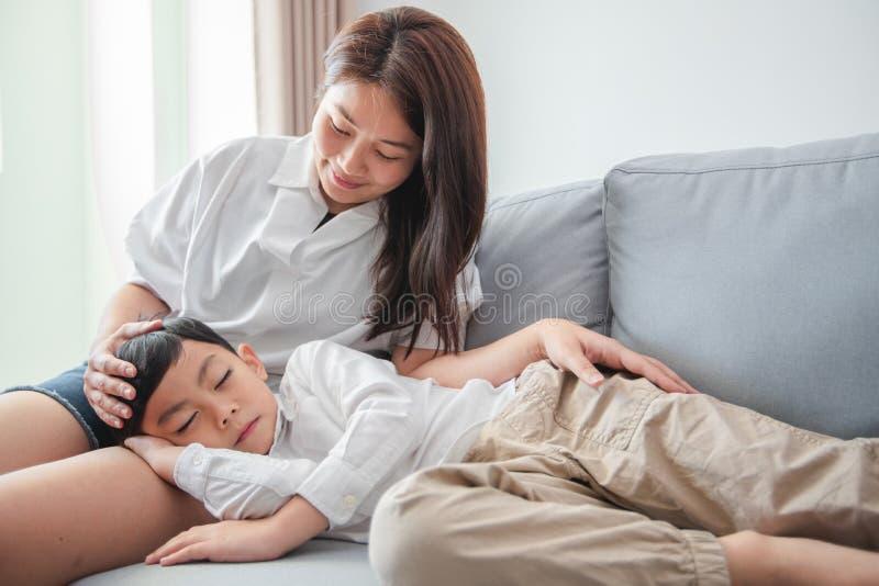 De gelukkige slaap van het bedtijdkind op bank met mamma stock afbeeldingen