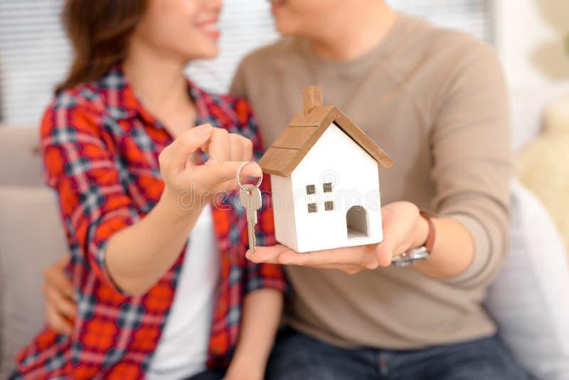 De gelukkige sleutels van de paarholding tot nieuwe huis en huis echte miniatuur - royalty-vrije stock afbeelding