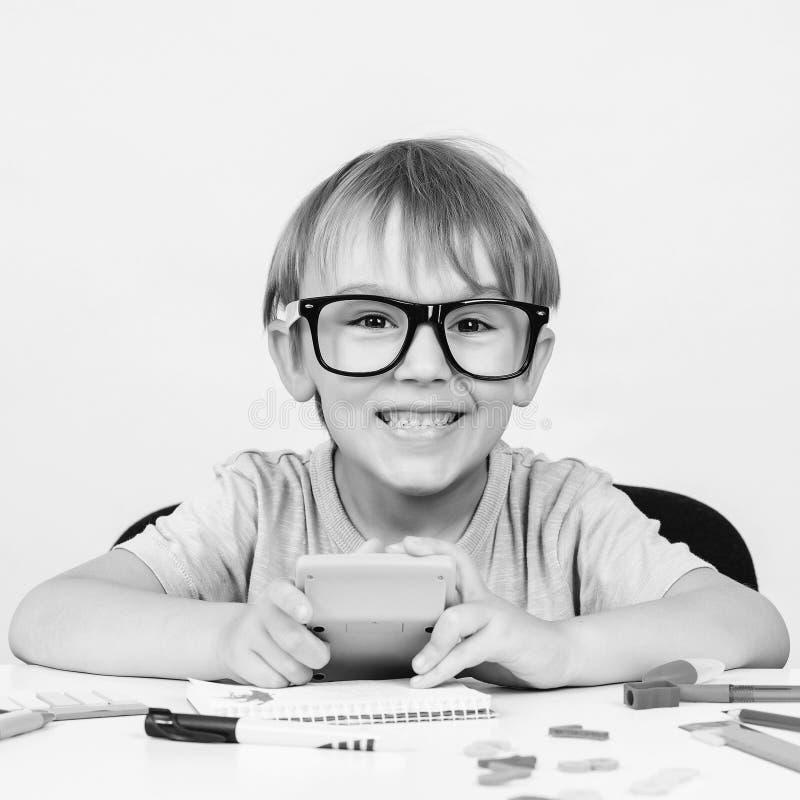 De gelukkige slimme jongen in grote glazen, zit bij bureau, kijkend aan camera Onderwijs Jonge geitjesidee genie Terug naar Schoo royalty-vrije stock foto