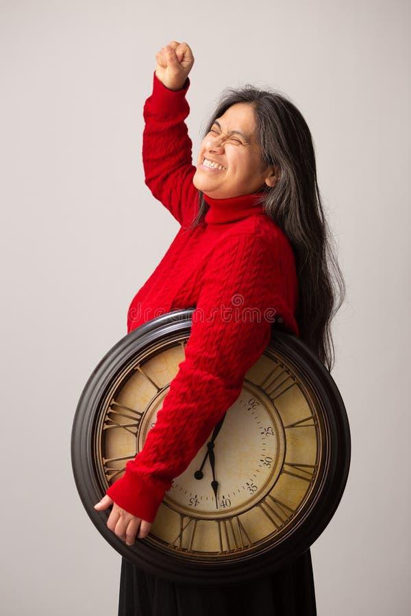 De gelukkige Spaanse Vrouw met Klok onder Wapen heft Vuist in Triumph op royalty-vrije stock foto's