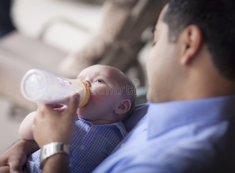 De gelukkige Spaanse Zoon van het Vaderbottle feeding his Gemengde Ras stock foto's
