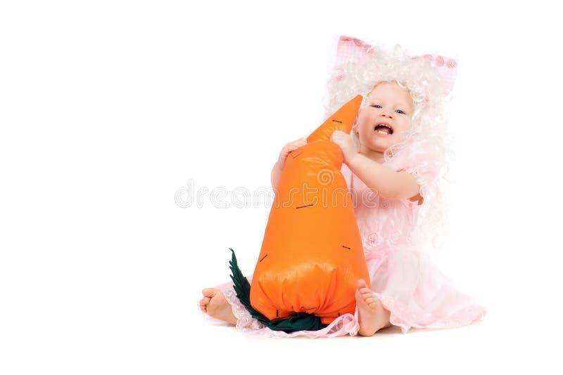 De gelukkige spelen van het babymeisje met een wortel royalty-vrije stock afbeeldingen