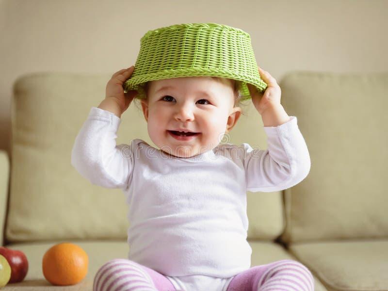De gelukkige spelen van het babymeisje met vruchten thuis stock foto