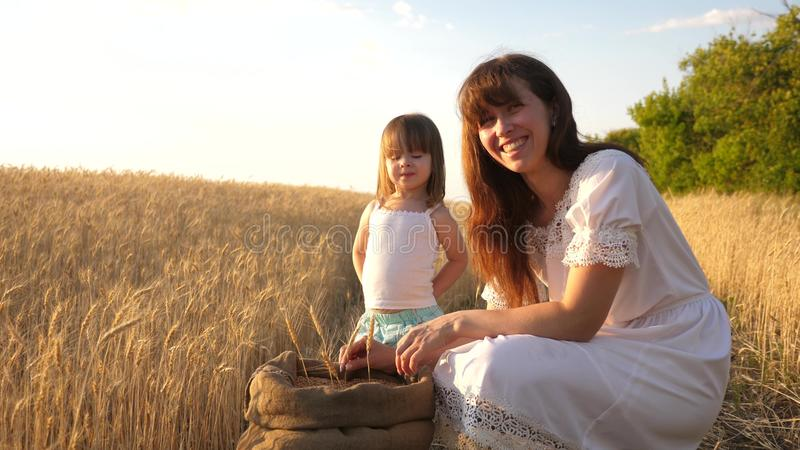De gelukkige spelen van de moederlandbouwer met weinig zoon, dochter op het gebied de moeder en weinig kind spelen met korrel in  stock afbeeldingen