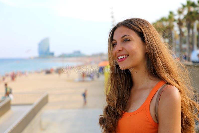 De gelukkige stadsvrouw gaat naar het strand bij zonsondergang Glimlachende jonge vrouw die naar het beroemde Barcelona strand va stock foto