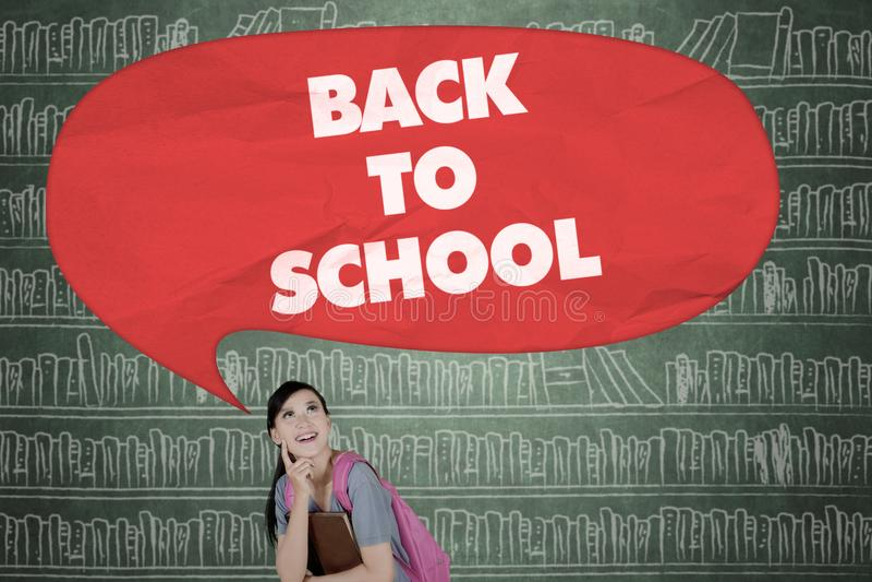 De gelukkige student bekijkt tekst van terug naar school royalty-vrije stock foto