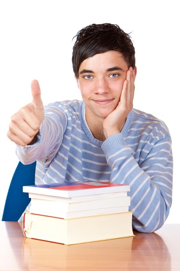 De gelukkige student met boeken toont duim royalty-vrije stock foto's