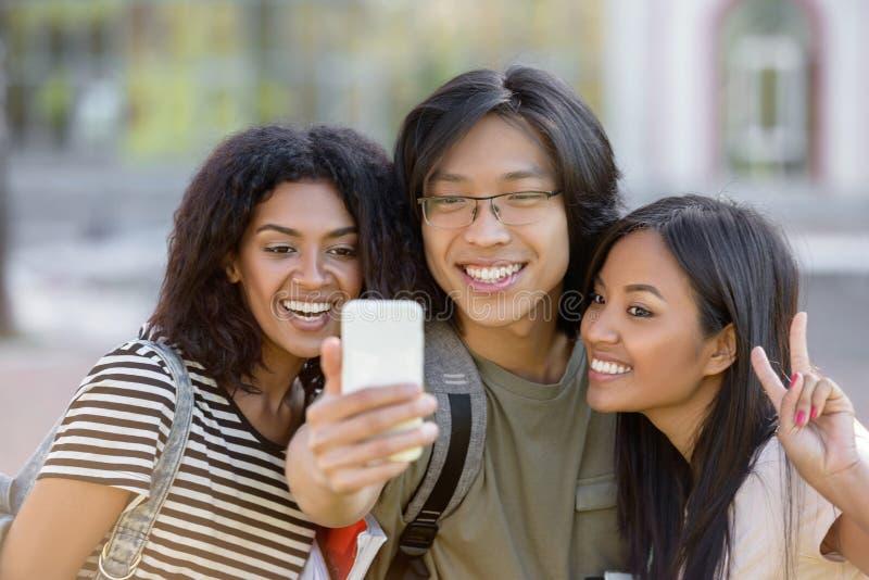 De gelukkige studenten die en maken in openlucht selfie bevinden zich royalty-vrije stock fotografie