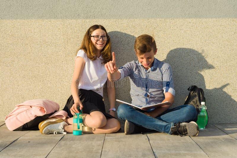 De gelukkige studenten op campusweg, tieners zitten op de grijze muur, lezen handboeken, drinken water, bekijken de tablet de jon stock foto