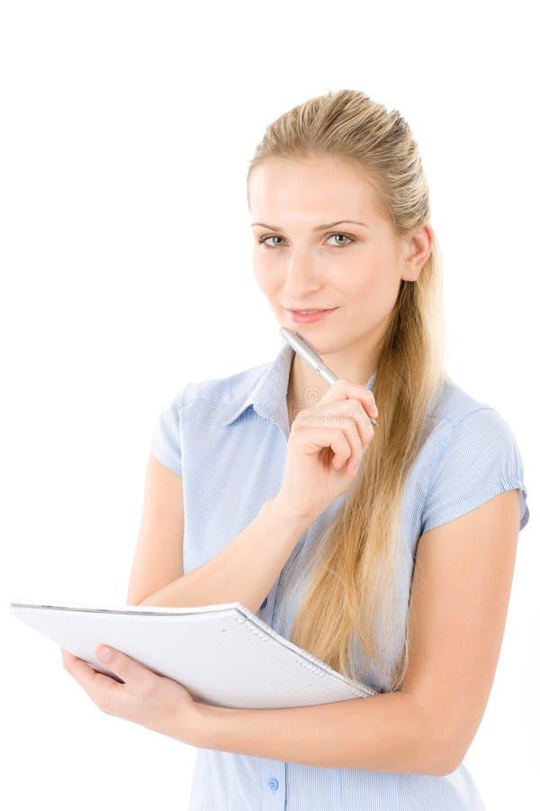 De gelukkige studentenvrouw schrijft nota's stock foto