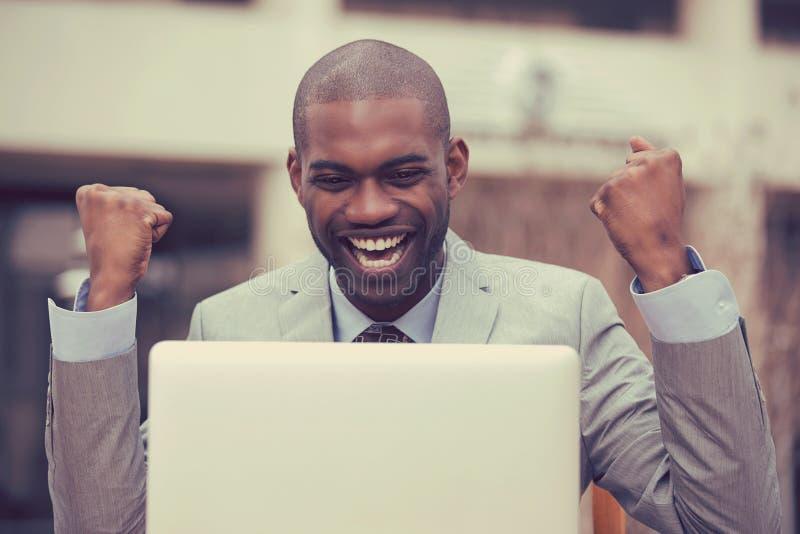 De gelukkige succesvolle mens met laptop viert succes buiten collectief bureau stock afbeelding