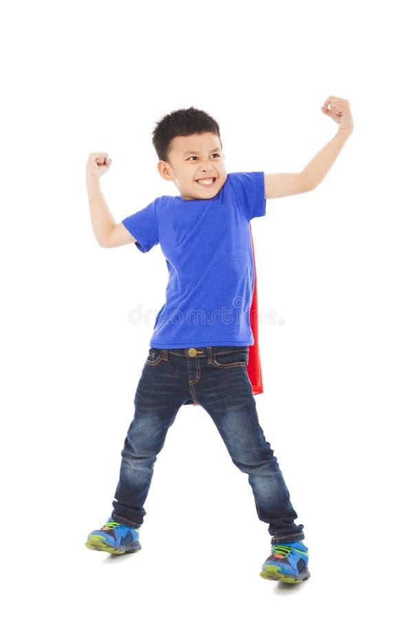 De gelukkige super jong geitjeheld imiteert superman stelt royalty-vrije stock foto's