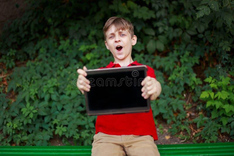 De gelukkige tablet van de jongensholding in handen Onderwijs, elektronisch spelenverslaving, kinderjaren, familie en mensenconce stock afbeelding