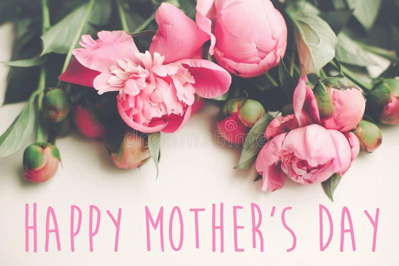 De gelukkige tekst van de moeder` s dag op roze pioenenboeket op rustiek wit stock afbeeldingen