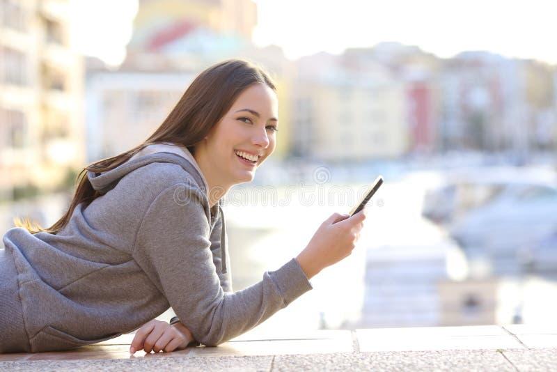 De gelukkige telefoon die van de tienerholding camera bekijken stock foto's