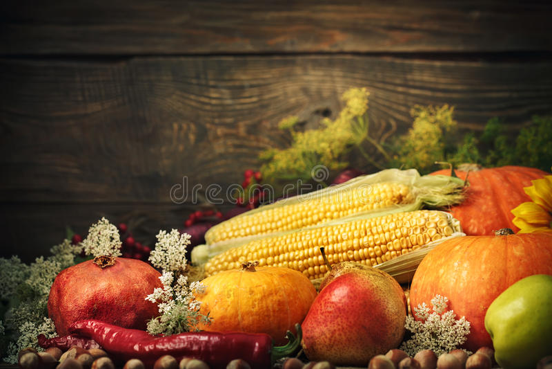 De gelukkige Thanksgiving dayachtergrond, de houten die lijst met Pompoenen wordt verfraaid, de Maïs, de vruchten en de herfst ga royalty-vrije stock foto's