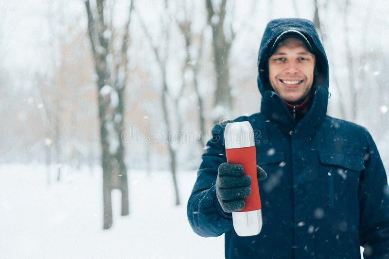 De gelukkige thermosflessen van de mensenholding in park met sneeuw Jonge mens die hete drank in bos in de wintertijd drinken stock afbeeldingen