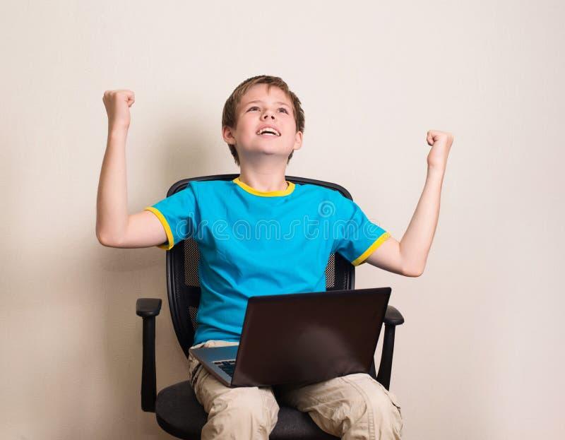 De gelukkige tienerjongen met laptop in het winnen stelt Succesjong geitje in offic stock fotografie