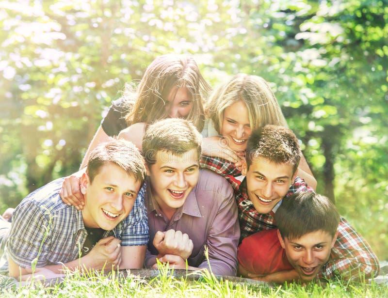 De gelukkige tienersvrienden hebben een pret in het de zomerpark stock fotografie