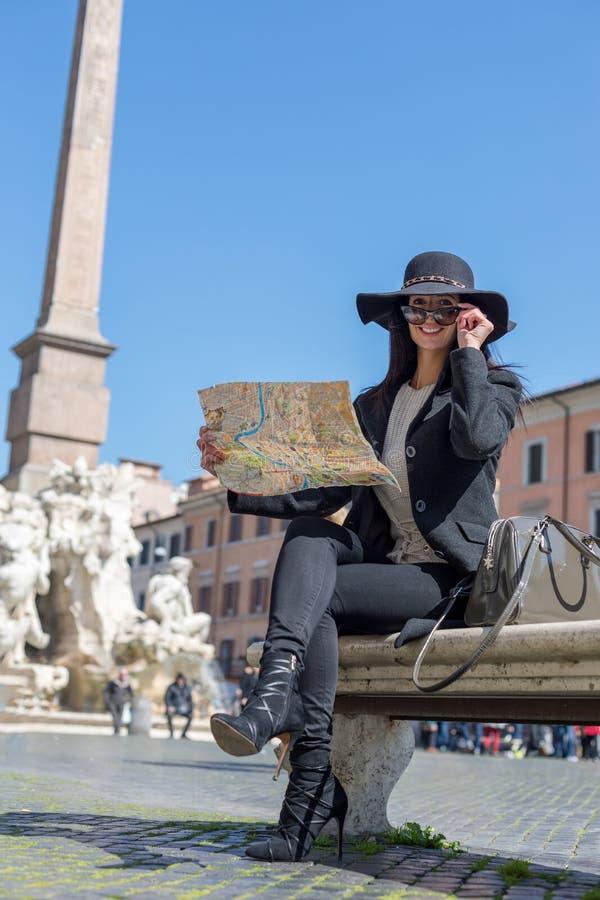 De gelukkige toerist van caucasionvrouwen houdt een kaart terug glimlachend royalty-vrije stock fotografie