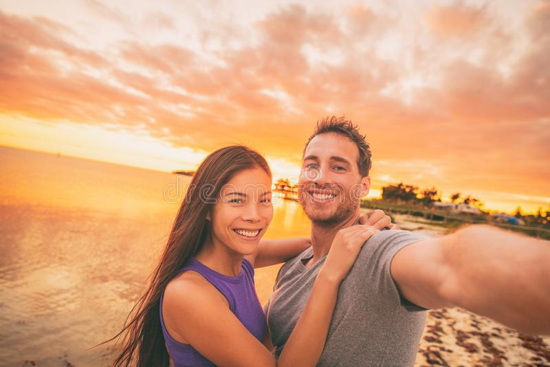 De gelukkige toeristen van het selfiepaar op de V.S. reizen het nemen van foto bij zonsondergang op het strand van Florida Glimla stock afbeelding