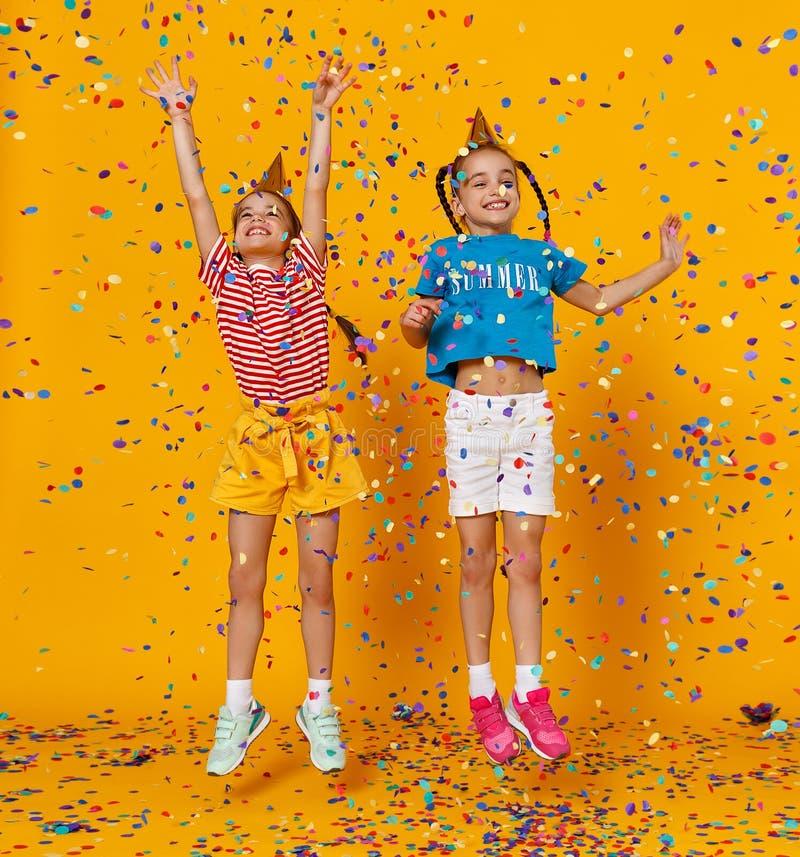De gelukkige tweelingen van kinderenmeisjes op vakantie die in multicolored confettien op geel springen stock foto