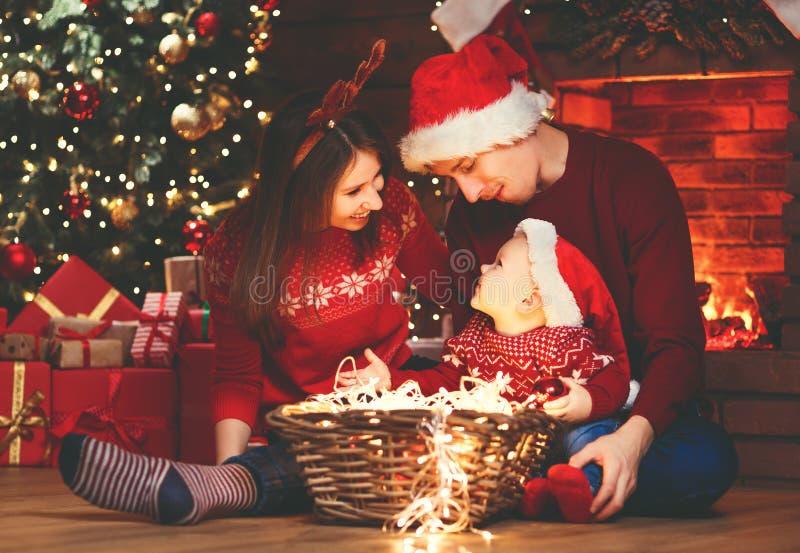 De de gelukkige vader en baby van de familiemoeder bij Kerstmisboom thuis stock afbeeldingen