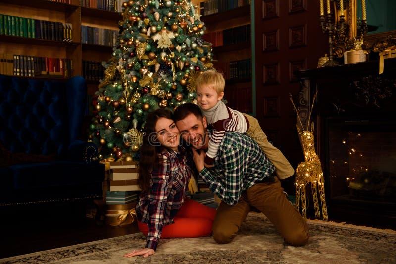 De de gelukkige vader en baby van de familiemoeder dichtbij Kerstmisboom thuis stock foto