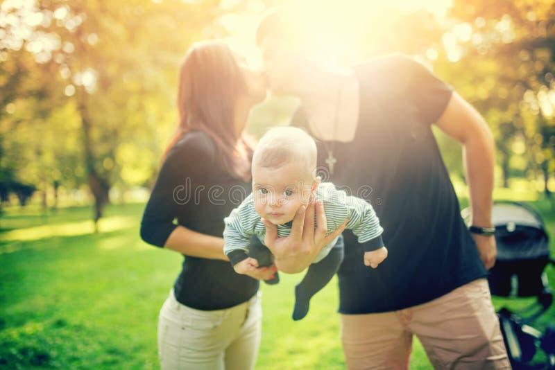 De gelukkige vader houdt pasgeboren baby die op wapen, de moeder van kind kussen gelukkige familie in park, pasgeboren jong geitj royalty-vrije stock afbeeldingen