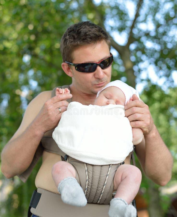 De gelukkige vader vervoert zijn baby in de drager. stock afbeelding
