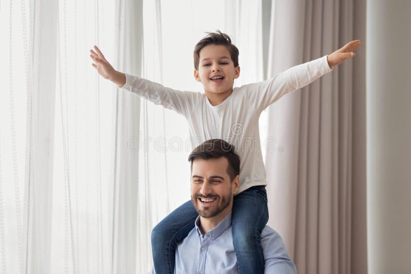 De gelukkige vader vervoert zoon die op schouders samen spelen stock foto's