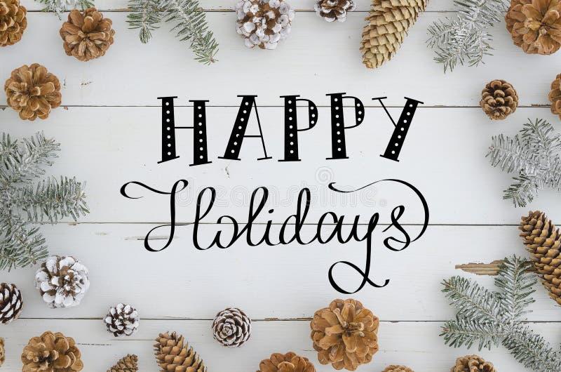 De gelukkige vakantie overhandigt het van letters voorzien op de winterachtergrond met pijnboom, spar, takken en kegels Modieus f stock fotografie