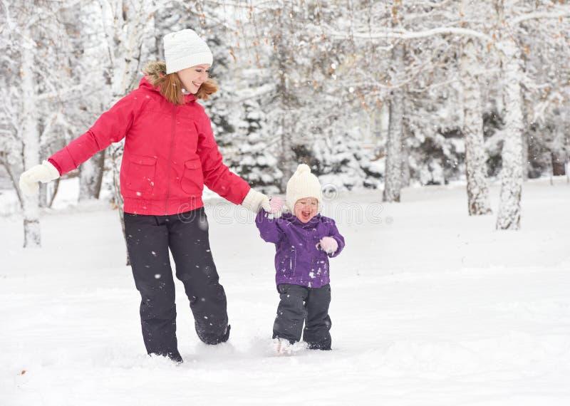 De gelukkige van de familiemoeder en baby looppas van de meisjesdochter, gang en het spelen in de wintersneeuw stock foto
