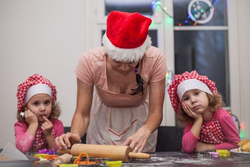 De gelukkige van familiemoeder en kinderen tweelingendochter bakt het kneden deeg in de keuken, bored tweelingmeisjes lettend op  stock afbeelding
