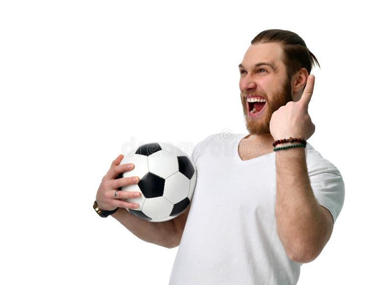 De gelukkige ventilator van het mensenvoetbal met bal toont nummer één het winnen vinger het glimlachen het vieren op wit stock foto