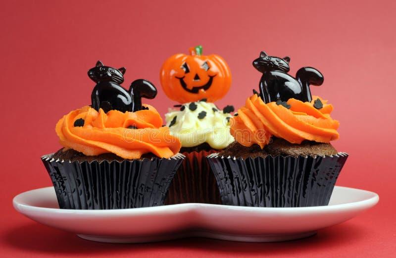 De gelukkige verfraaide sinaasappel en de zwarte van Halloween cupcakes stock foto