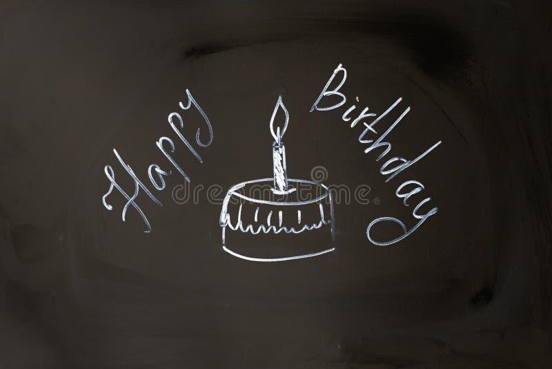 De gelukkige verjaardag van de krijtinschrijving cupcake met kaars stock foto's