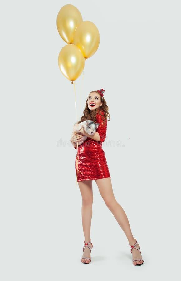De gelukkige verraste vrouw in rood schittert kleding houdend weinig varken en gele ballons op witte achtergrond stock foto's