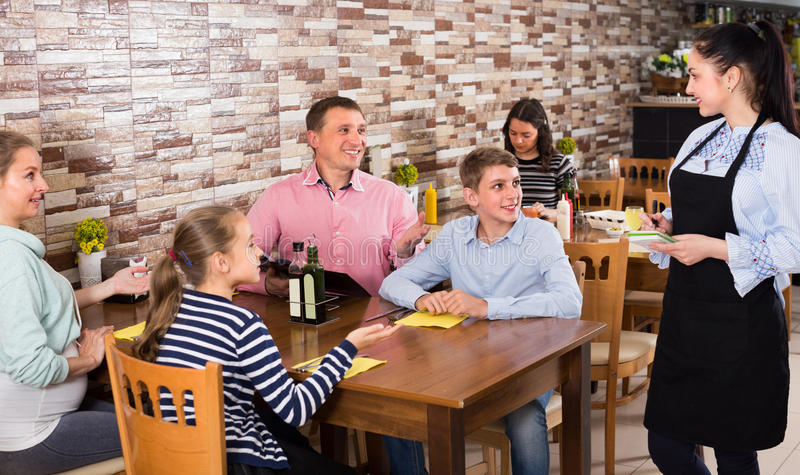De gelukkige volwassenen met kinderen geven orde aan vrolijke serveerster royalty-vrije stock foto
